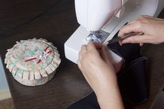 Nähende Kleidung durch einen einzelnen Unternehmer Eine Frau arbeitet an einer Nähmaschine Staples die Schnittelemente des Produk Lizenzfreies Stockfoto