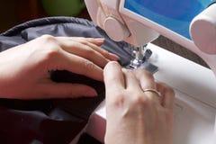 Nähende Kleidung durch einen einzelnen Unternehmer Eine Frau arbeitet an einer Nähmaschine Staples die Schnittelemente des Produk Stockbilder