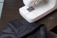 Nähende Kleidung durch einen einzelnen Unternehmer Eine Frau arbeitet an einer Nähmaschine Staples die Schnittelemente des Produk Lizenzfreie Stockfotografie