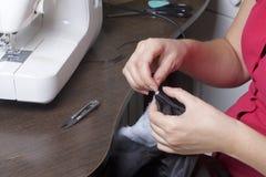 Nähende Kleidung durch einen einzelnen Unternehmer Eine Frau arbeitet an einer Nähmaschine Staples die Schnittelemente des Produk Stockfoto