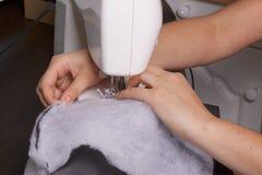 Nähende Kleidung durch einen einzelnen Unternehmer Eine Frau arbeitet an einer Nähmaschine Staples die Schnittelemente des Produk Stockfotografie