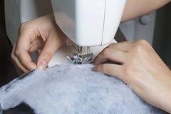 Nähende Kleidung durch einen einzelnen Unternehmer Eine Frau arbeitet an einer Nähmaschine Staples die Schnittelemente des Produk Lizenzfreie Stockbilder