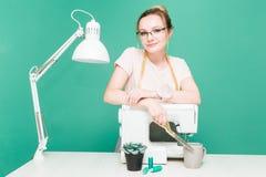 Nähende Werkstatt Näherin bei der Arbeit Porträt einer jungen Damenschneiderin auf einem farbigen Hintergrund stockfotos