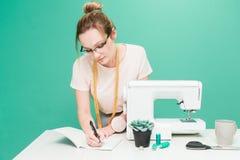 Nähende Werkstatt Näherin bei der Arbeit Porträt einer jungen Damenschneiderin mit Notizbuch auf einem farbigen Hintergrund lizenzfreies stockfoto