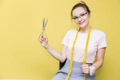 Nähende Werkstatt Näherin bei der Arbeit Porträt einer jungen Damenschneiderin mit Scheren auf einem farbigen Hintergrund lizenzfreie stockfotografie