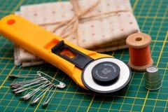 Nähende Werkzeuge des Patchworks auf grüner Matte Stockfotos