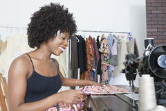 Nähender Stoff der weiblichen Damenschneiderin des Afroamerikaners auf Nähmaschine Lizenzfreie Stockfotografie