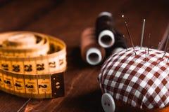 Nähender Zentimeter, Nadel und Thread auf braunem Holztisch lizenzfreies stockfoto