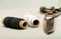 Nähendes Gewebe oder Stoff Arbeitstabelle eines Schneiders Scherenspulenthread und natürliches Gewebe Feld der flachen Tiefe Stockfotos