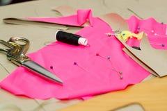 Nähendes Gewebe oder Stoff Arbeitstabelle eines Schneiders Textilwerkzeuge Scissors Garnrolle, messende Bänder und natürlich Lizenzfreie Stockfotos