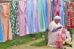 Nähendes Kleid der Zulu- Frau vor hell farbigen Kleidern auf Anzeige im Zulu- Dorf im Zululand, Südafrika Stockfotografie