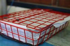 Näher an dem Sieb setzen Sie ein rotes Dokument in das Büro ein lizenzfreies stockfoto