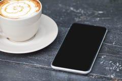 Näher herauf den Handy auf einer schwarzen hölzernen Tabelle Lizenzfreie Stockfotos