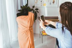 Näherin, die Foto des Kleides auf Mannequin macht stockfotos