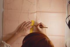 Näherin zeichnet das Muster auf Zeichenpapier mit Maßeinteilung im Studio stockfotografie