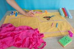 Näherinhände auf der Arbeitstabelle mit Muster und messendem Band Lizenzfreies Stockfoto