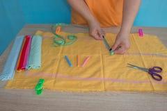 Näherinhände auf der Arbeitstabelle mit Muster und messendem Band Stockbild