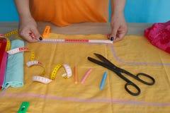 Näherinhände auf der Arbeitstabelle mit Muster und messendem Band Stockfotografie