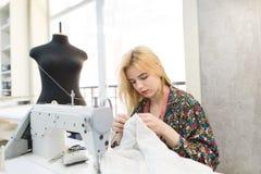 Näherinmädchen sitzt am Arbeitsplatz nahe einer Nähmaschine und näht einen weißen Stoff mit ihren Händen stockbild
