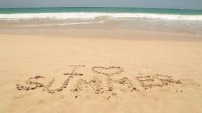 Nähernde Wörter des Meereswogen I lieben den Sommer, der in Sand auf Strand geschrieben wird stock video footage