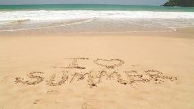 Nähernde Wörter des Meereswogen I lieben den Sommer, der in Sand auf Strand geschrieben wird stock video
