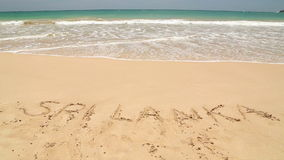 Nähernde Wörter Sri Lanka des Meereswogen geschrieben in Sand auf Strand stock video