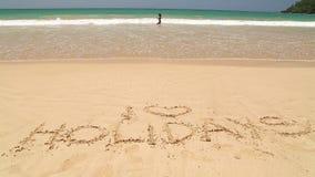 Nähernde Wortfeiertage des Meereswogen geschrieben in Sand auf Strand stock video