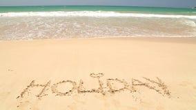 Nähernder Wortfeiertag des Meereswogen geschrieben in Sand auf Strand stock video footage