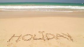 Nähernder Wortfeiertag des Meereswogen geschrieben in Sand auf Strand stock footage