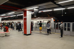 Nähernder Zug mit den Passagieren, die auf Plattform Hong Kongs MTR warten Stockfoto