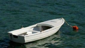 Näherte sich einem weißen hölzernen Boot mit orange Boje im Wasser stock video footage