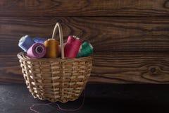 Nähgarne in den verschiedenen Farben Rosa, Blau, Grün, rot Threads im Weidenkorb auf einem alten hölzernen Hintergrund Konzept de Lizenzfreies Stockfoto