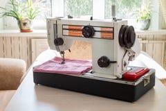 Nähmaschine der Weinlese auf einem Holztisch lizenzfreie stockfotografie