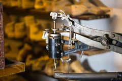 Nähmaschine in einer Schuhwerkstatt, Schuh dauert im Hintergrund stockfoto
