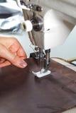 Nähmaschine mit den Händen der Frau Lizenzfreie Stockfotografie