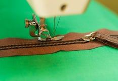 Nähmaschine mit einer großen Nadel bereit, die Arbeit über einen dunklen Reißverschluss, grüner Hintergrund zu beginnen Lizenzfreie Stockbilder