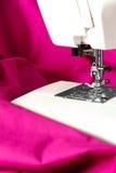 Nähmaschine und ein rosafarbenes Gewebe Lizenzfreie Stockfotografie