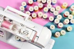 Nähmaschine und Gewinderollen, Gruppe des bunten Threads auf nähendem Schreibtisch lizenzfreie stockbilder