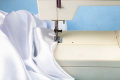 Nähmaschine und weißer Satin lizenzfreie stockbilder