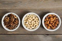 Nähren Sie Nüsse in den weißen Schüsseln auf einem Holztisch Lizenzfreie Stockfotografie