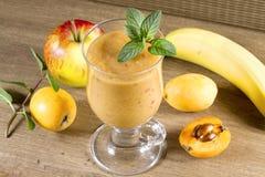 Nähren Sie Smoothies von den Loquats, von den Bananen und von den Äpfeln Stockfoto
