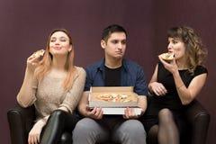 Nährende Aussehung des Mannes wie Freundinnen essen Pizza stockfotos