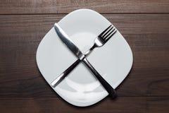Nährende weiße Platte des Konzeptes mit Messer und Gabel Lizenzfreies Stockfoto