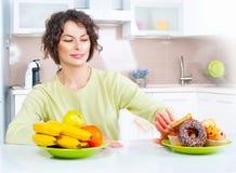 Nährendes Konzept Junge Frau, die zwischen Früchten und Bonbons wählt Stockbilder