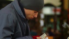 När du äter tiggaren räknar stal pengar, dollar som äter den fattiga mannen arkivfilmer