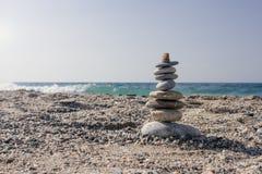 När du balanserar stenar ställde in en överst av kusten Arkivbilder