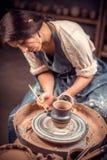 När du charmar den unga och gladlynta kvinnan visar processen av att göra keramisk disk genom att använda den gamla teknologin ha arkivbilder