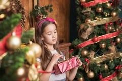 När du drömmer lilla flickan som bär den röda huvudbindeln, öppnar gåvan nära julträd arkivbilder