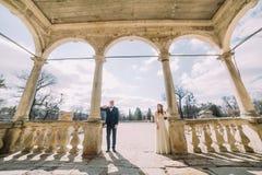 När du gifta sig par som poserar på välvd terrass av antikviteten, fördärvade slotten royaltyfri foto