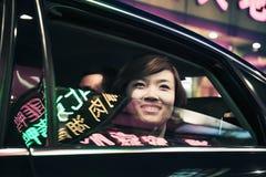 När du ler affärskvinnan med bilfönstret rullade ner att se ut på utelivet i Peking Arkivbild
